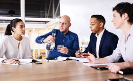 Powerful young woman talking with the attention of three colleagues. Corporate meeting between four eclectic business executives, where a beautiful young royalty free stock photography
