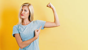 Powerful young woman. On a yellow background Royalty Free Stock Photos