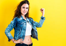 Powerful young woman. On a yellow background Stock Photos