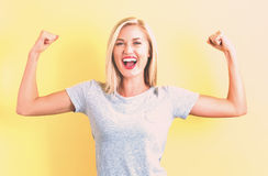Powerful young woman. On a yellow background Royalty Free Stock Images