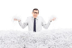 Powerless employee holding bunch of shredded paper. Isolated on white background Stock Photos