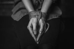 Powerless terrified woman unable to move. Motionless. Trapped abducted scared girl being imprisoned and sitting in a dark place with her hands tied up Royalty Free Stock Photo