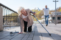 Powerless woman falling in the street. Be more attentive to others. Dolorous helpless ill lady feeling pain in the stomach and dropping her crutches while aged Royalty Free Stock Images
