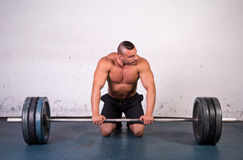 Powerlifter. Real powerlifter preparing to lift a heavy dumbbell stock image