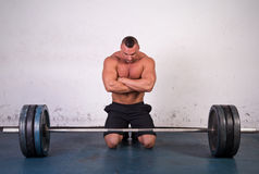 Powerlifter. Strong man preparing to lift a heavy dumbbell Royalty Free Stock Images