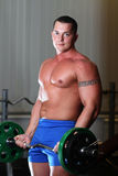 Powerlifter with barbell in gym. Young pumped power-lifter with a tattoo on his bicep exercising in gym Royalty Free Stock Photos