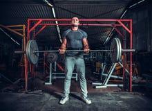 Powerlifter med starka armar som lyfter vikter Arkivbild