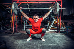 Powerlifter with strong arms lifting weights Stock Photos