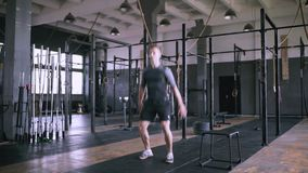 Male fitness instructor showing squat exercise at modern plase. Powerlifting effective jumps. Male fitness instructor showing squat exercise at loft plase stock video footage