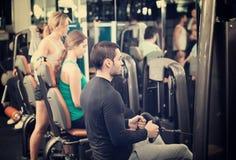 Powerlifting en las máquinas en club de fitness Imágenes de archivo libres de regalías