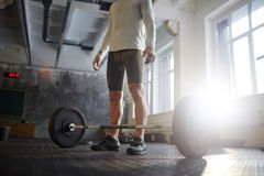 Powerlifting in Gym. Portrait of unrecognizable strong muscular man ready to lift heavy barbell from floor  during powerlifting workout in sunlit gym Royalty Free Stock Photo