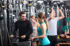 Powerlifting on machines in fitness club. Group of positive young adults doing powerlifting on machines in fitness club Stock Photography