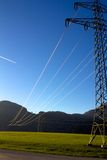 Powerline glow in sunset. Plane on blue sky Royalty Free Stock Photos