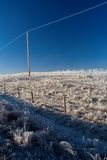 Powerline Hoarfrost. A powerline penetrates a deep blue sky on a frosty winter morning stock photo