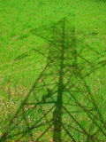 Powerline. Shadow on the grass. Shadow from powerline on green grass field royalty free stock photography