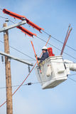 Powerline worker. A lineman high in a truck bucket works to repair electric lines stock image