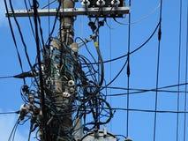 Powerlineisolatorer, kontaktdon och tilltrasslade trådar på elektrisk pol Arkivbild