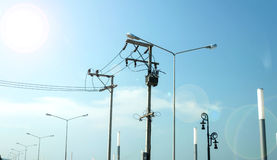 Powerlines приближают к свету лампы и солнца Стоковое Фото