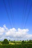 Powerlines che attraversano sopra i campi e la campagna fotografie stock libere da diritti