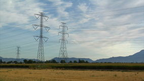 Powerlines e montagne con il timelapse del campo di mais video d archivio