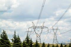 Powerlines e piloni ad alta tensione contro il cielo nuvoloso Fotografia Stock Libera da Diritti