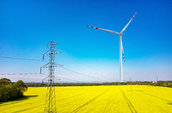 Powerlines and windmill on colza field Royalty Free Stock Photos