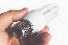 Powersave or electric energy-saving lamp. Powersave or electric energy-saving fluorescent lamp bulb in male hand close up, selective focus royalty free stock images