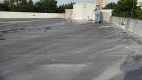 Powerwashing commercial PVC flat roof. Roofing crew Powerwashing a commercial PVC flat roof, pressure washing, roof cleaning royalty free stock images