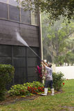 Powerwashing before painting. Crew member powerwashing a wall before painting Royalty Free Stock Photos
