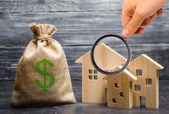 Powiększać - szkło jest przyglądający blisko torby z pieniądze trzy domu nieruchomości inwestycja i nabycie obraz royalty free