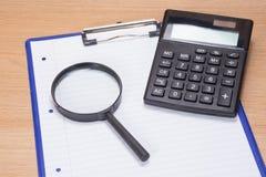 Powiększać - szkło i kalkulator na schowku obraz royalty free