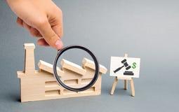 Powiększać - szkło jest przyglądającym postaci fabryką, stojakiem z wizerunkiem aukcja i Prywatyzacja państwowe fabryki obraz stock