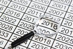 Powiększać - szkło na liczbie nowy rok przy 2018 Zdjęcie Royalty Free