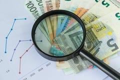 Powiększać - szkło na stosie Euro banknoty z drukowanym barem przypala Obrazy Royalty Free