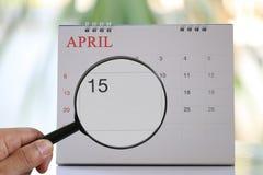 Powiększać - szkło w ręce na kalendarzu ty możesz patrzeć Fifteenth dzień zdjęcia royalty free