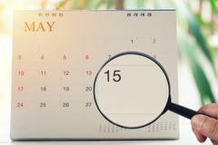 Powiększać - szkło w ręce na kalendarzu ty możesz patrzeć Fifteenth dzień obrazy stock