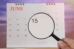 Powiększać - szkło w ręce na kalendarzu ty możesz patrzeć Fifteenth dzień zdjęcie stock