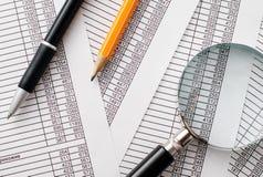 Powiększający na górze raportów - szkło, pióro i ołówek, Zdjęcia Stock