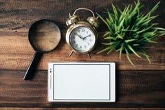 Powiększający - szkło, zegar, zielona roślina i cyfrowa pastylka z pustym ekranem na drewnianym stołowym tle, Obraz Royalty Free