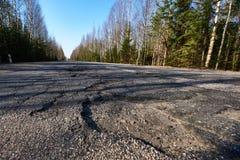 Powierzchnia autostrada iluminuje kosymi promieniami słońce Wielcy wyboje na drodze Narosły zagrożenia zagrożenie bieda zdjęcie stock