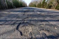 Powierzchnia autostrada iluminuje kosymi promieniami słońce Wielcy wyboje na drodze Narosły zagrożenia zagrożenie bieda obraz stock