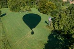 Powietrza balloonå cień na zieleni polu z kryjówką Fotografia Stock