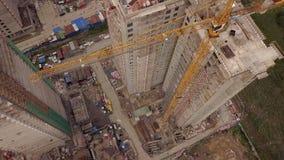Powietrzna dzień komarnica nad w budowie nowymi nowożytnymi budynek pracy budowniczymi i technicals z żurawiem zdjęcie wideo