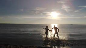 Powietrzna strzelanina od latającego trutnia młody szczęśliwy para bieg na plaży denny mienia chełbotanie i ręki zdjęcie wideo