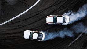 Powietrzni odgórnego widoku dwa samochody dryfują bitwę na biegowym śladzie, Dwa samochodu półdupka zdjęcia stock