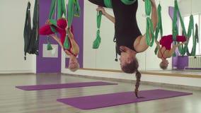 Powietrzny joga Dwa kobiety opaść w hamakach do góry nogami zbiory wideo