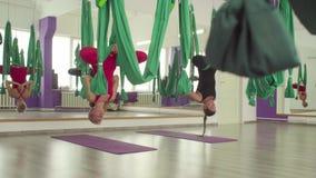 Powietrzny joga Dwa kobiety opa?? w hamakach do g?ry nogami zbiory