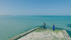 Powietrzny krótkopęd Blondynki młodej kobiety śpiew na wybrzeżu, plaży lub quay z mężczyzna muzyka keyboardzisty Seksowną dziewcz zdjęcie wideo