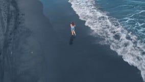 Powietrzny materiał filmowy ocean plaża z czarnym piaskiem i pienić się macha przy zmierzchem na Bali z piękną dziewczyną, cudown zbiory wideo
