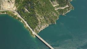 Powietrzny materiał filmowy samochodowy jeżdżenie nad mostem na Piva jeziorze zdjęcie wideo